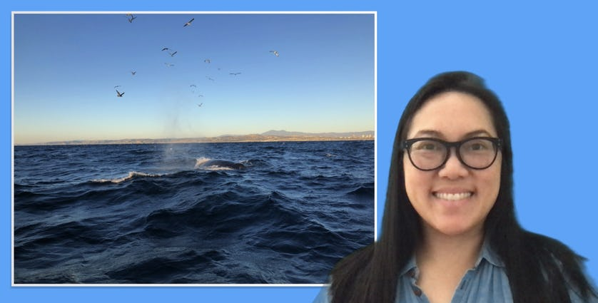 Woman smiling in front of a picture of the ocean