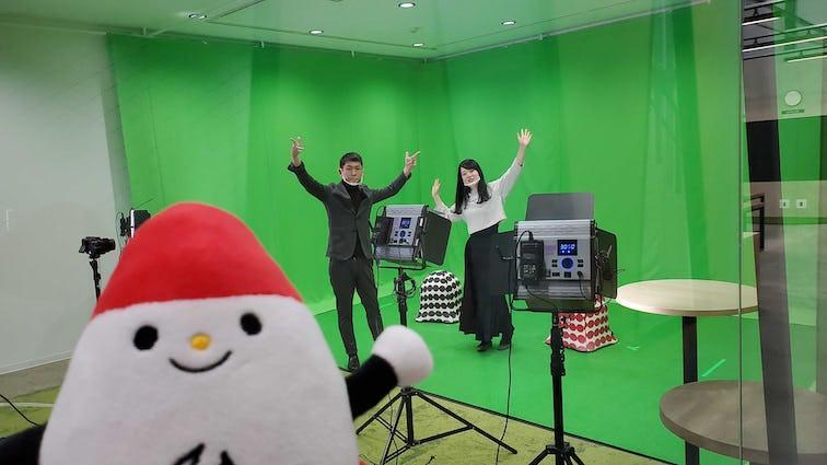 グリーンスクリーンをバックにポーズを撮る男性・女性とキャラクター