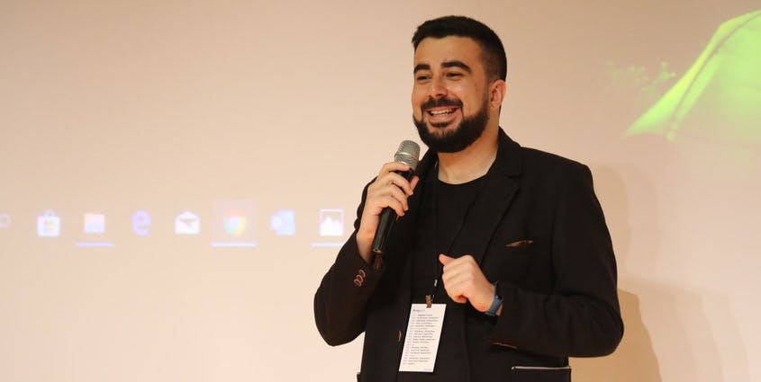 Photo of Çağrı Menteş holding a microphone giving a presentation in front of a projector.