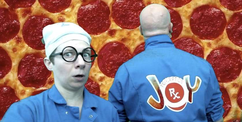 Two clowns standing in front of a pepperoni pizza close-up