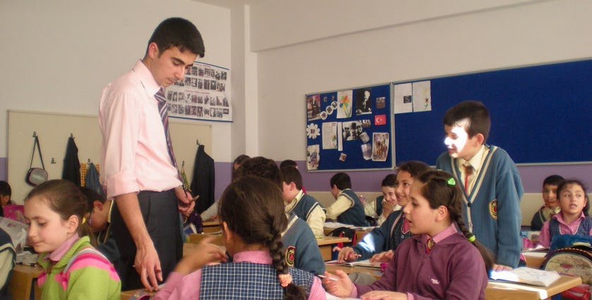Menteş wears a suit and tie teaching students in a classroom.