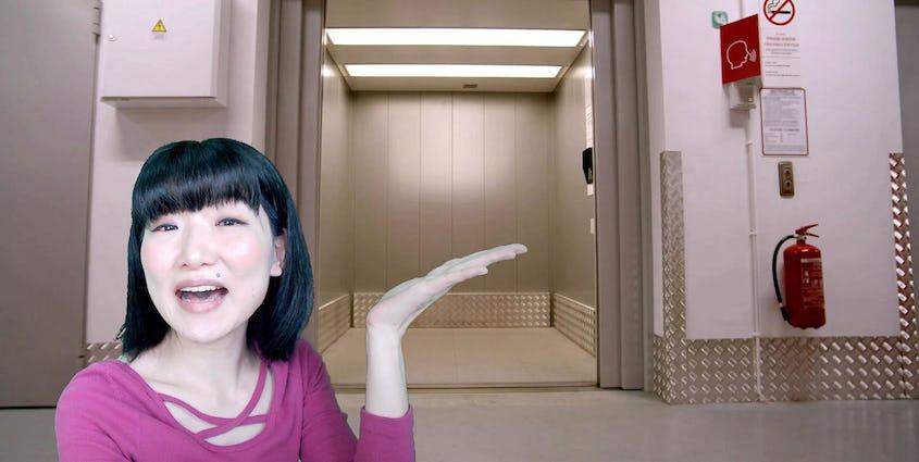 エレベーターの前で演技をする女性
