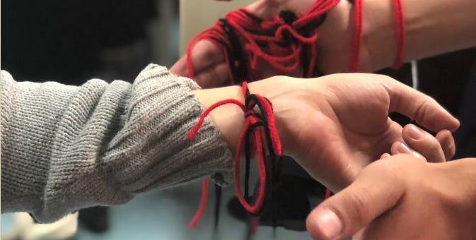 Hands with red and black yarn tied around wrists