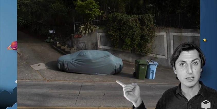 カバーのかかった駐車中の車を差す人