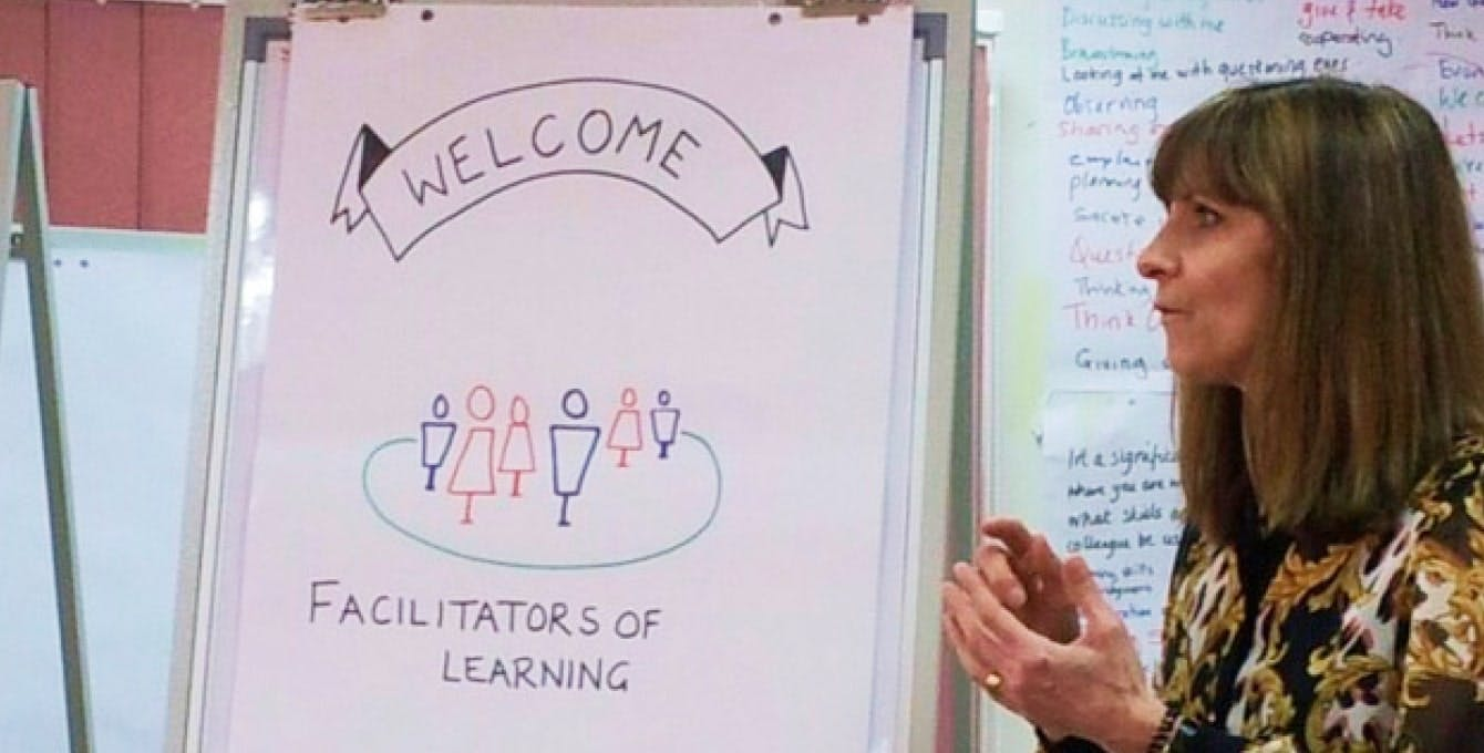 Joyce Matthews standing at the flip chart that says Welcome Facilitators of Learning