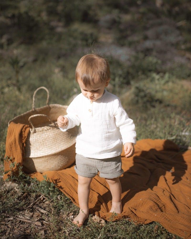 Et barn går rundt på et tæppe der ligger på en græsplæne