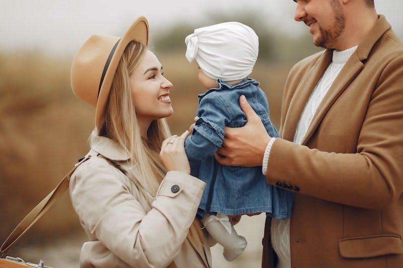 Mor og far holder baby imellem sig og smiler