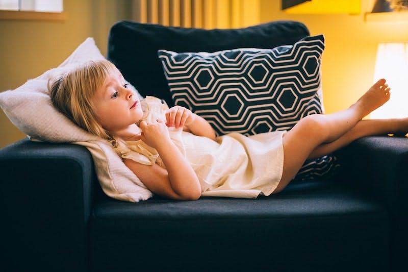 Et barn ligger på tværs i en læne stol og tænker