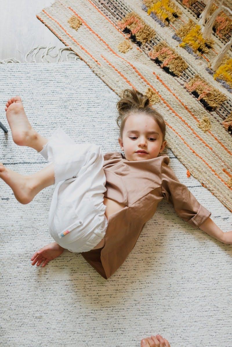 Et barn ligger på et tæppe og leger