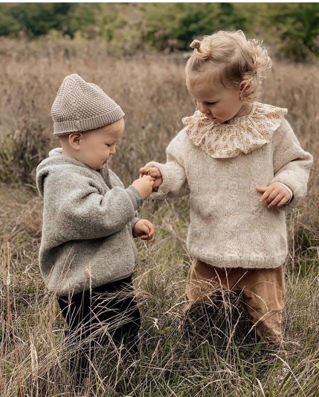 2 børn er på en græsplæne og kigger på en blomst