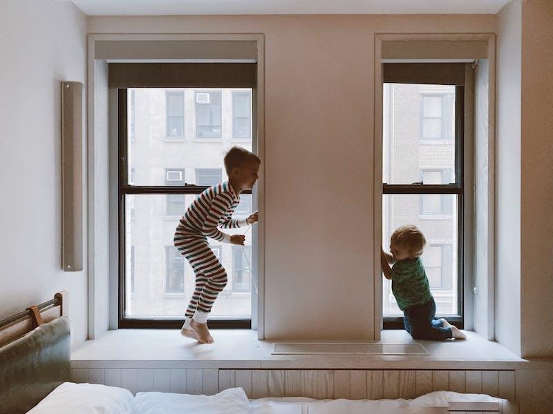 2 børn hopper i vindueskarmen