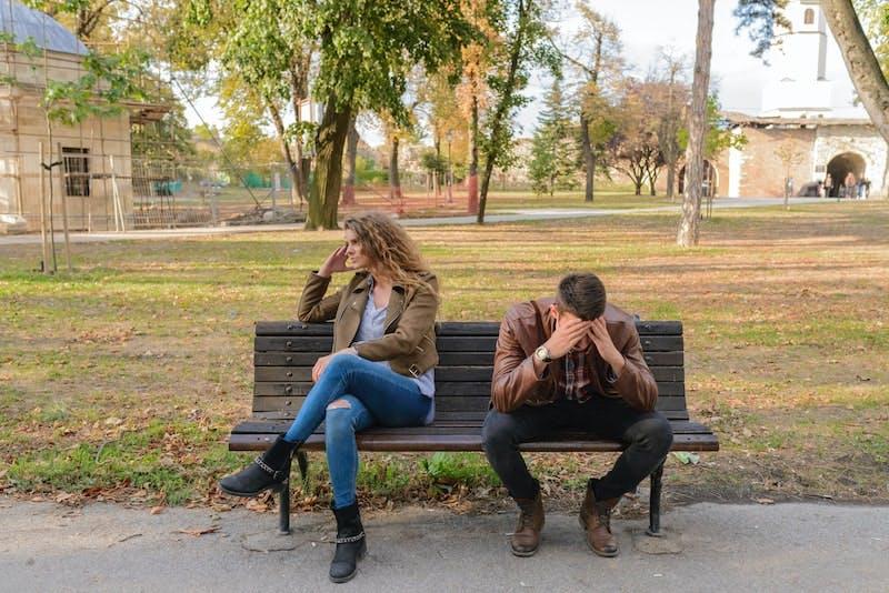 2 forældre sidder på en bænk og er frustreret