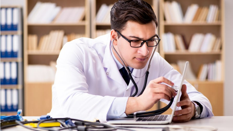 a doctor with stethoscope looking at his computer