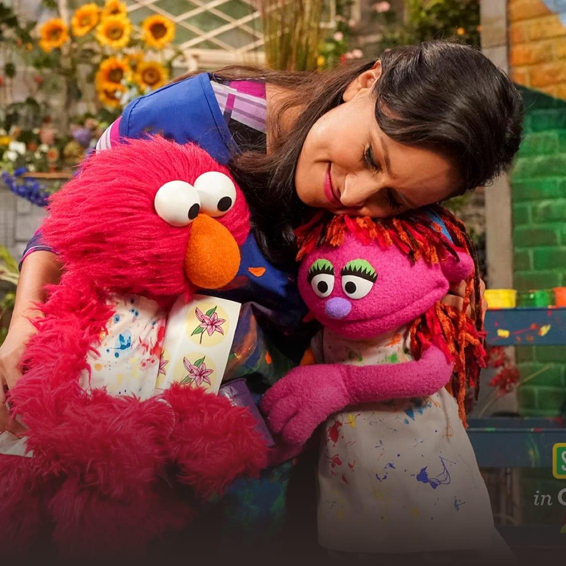 a woman huging Elmo and Abby Cadabby