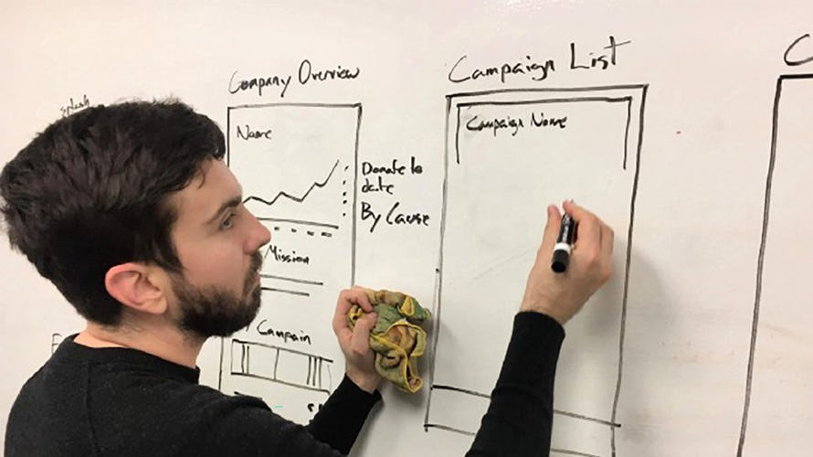 Nicholas drawing some wireframes on a white board