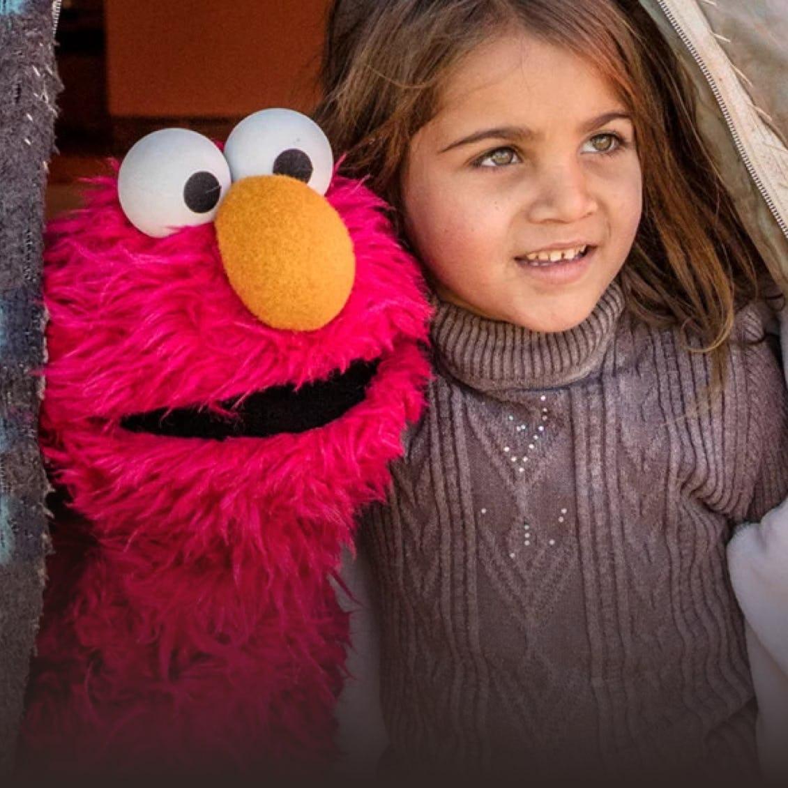a kid hunging Elmo
