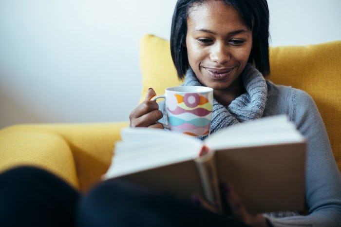 a woman reading a book while she's drinking a coffee and smilling