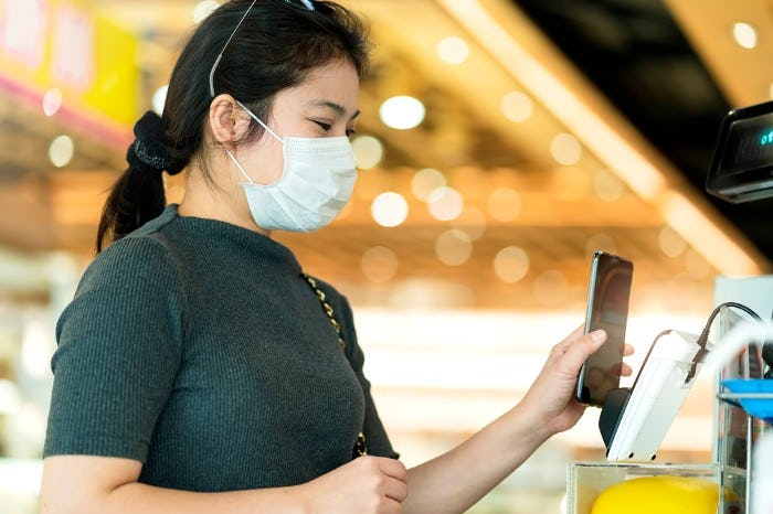 a woman with a mask using her phone to pay