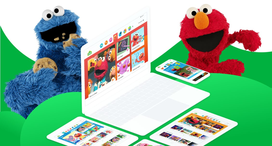 The cookie monster and Elmo in a green and white background with a computer and phones with the Sesame site in it.