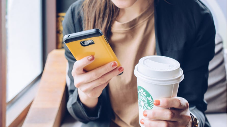 A young woman holding a cellphone and a Starbucks cup