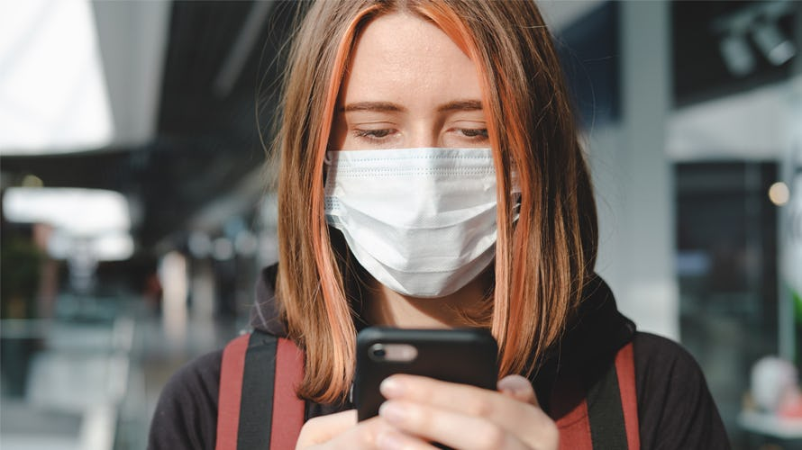 a woman with a mask looking at her phone