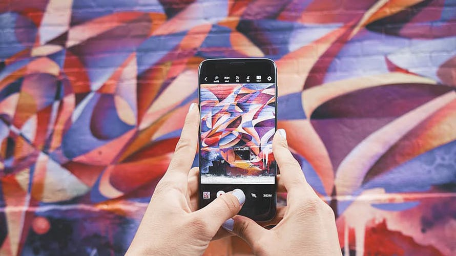A woman taking a photo of a graffiti