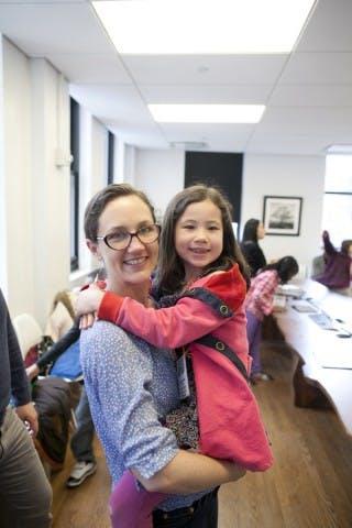 Kristin Vogel, holding a smilling kid