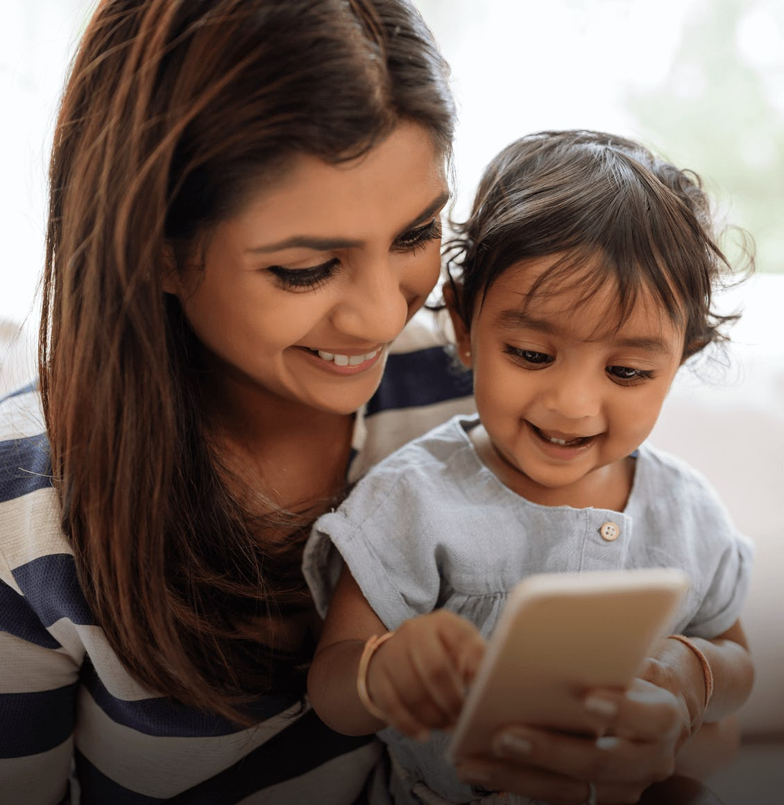a mother with her son looking at a phone