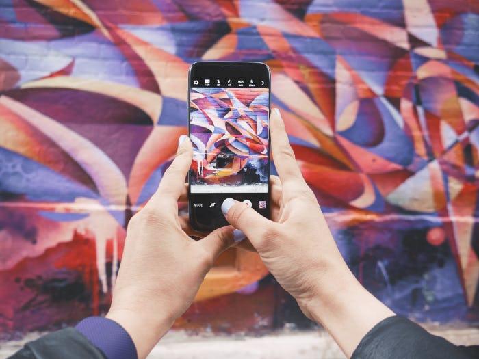 a homan taking a photo of a mural