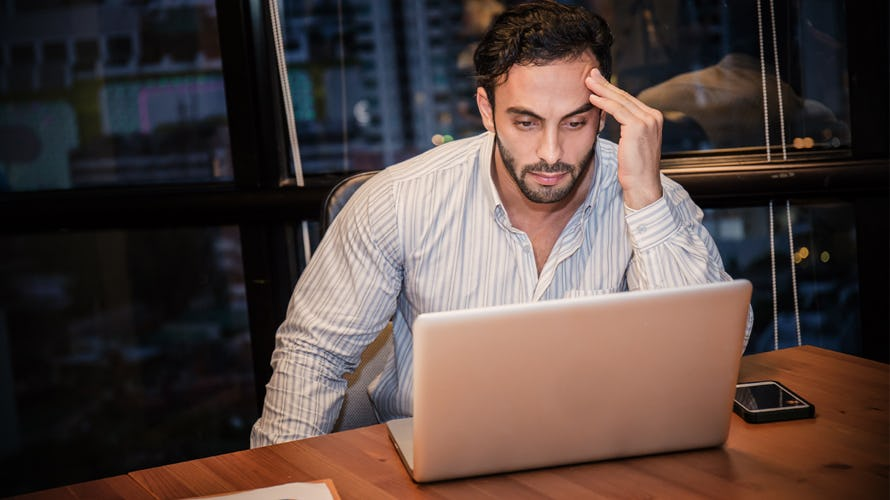 A man looking at his computer in frustration