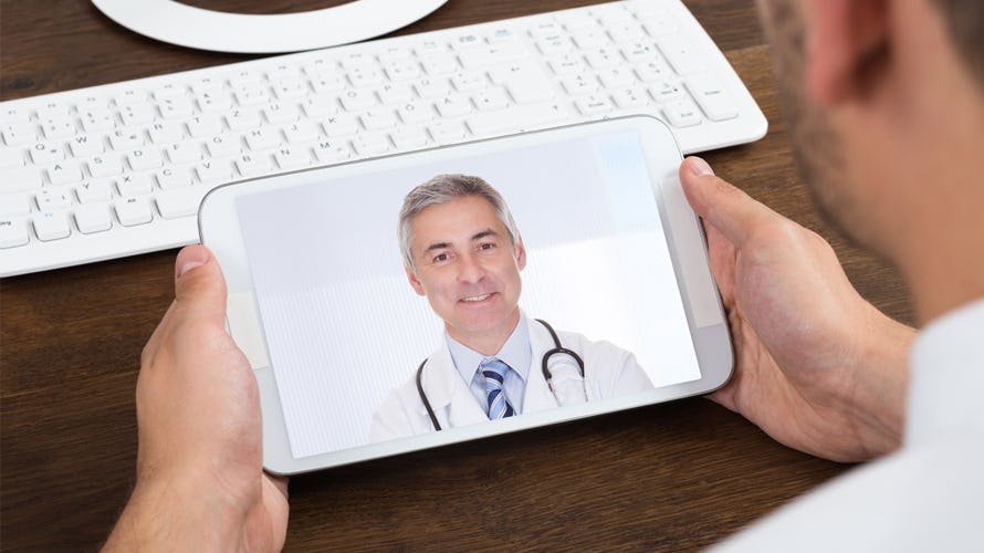 a man looking on a video call with his doctor