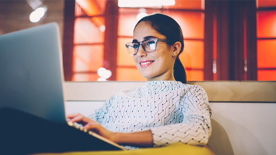A woman looking at her computer smiling