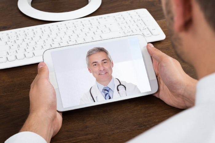 a man looking at his phone talking with his doctor though a video call