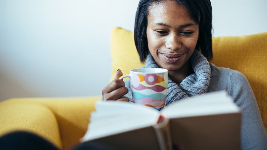 A woman reading a book with a cup of coffee on her hand