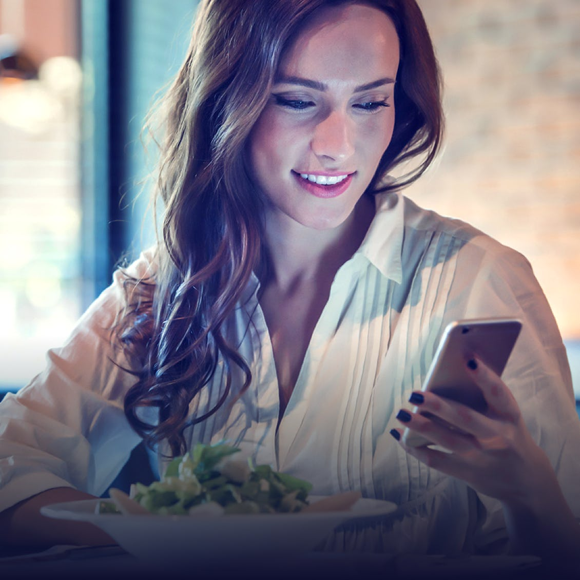 a woman looking at her phone and eating a salad