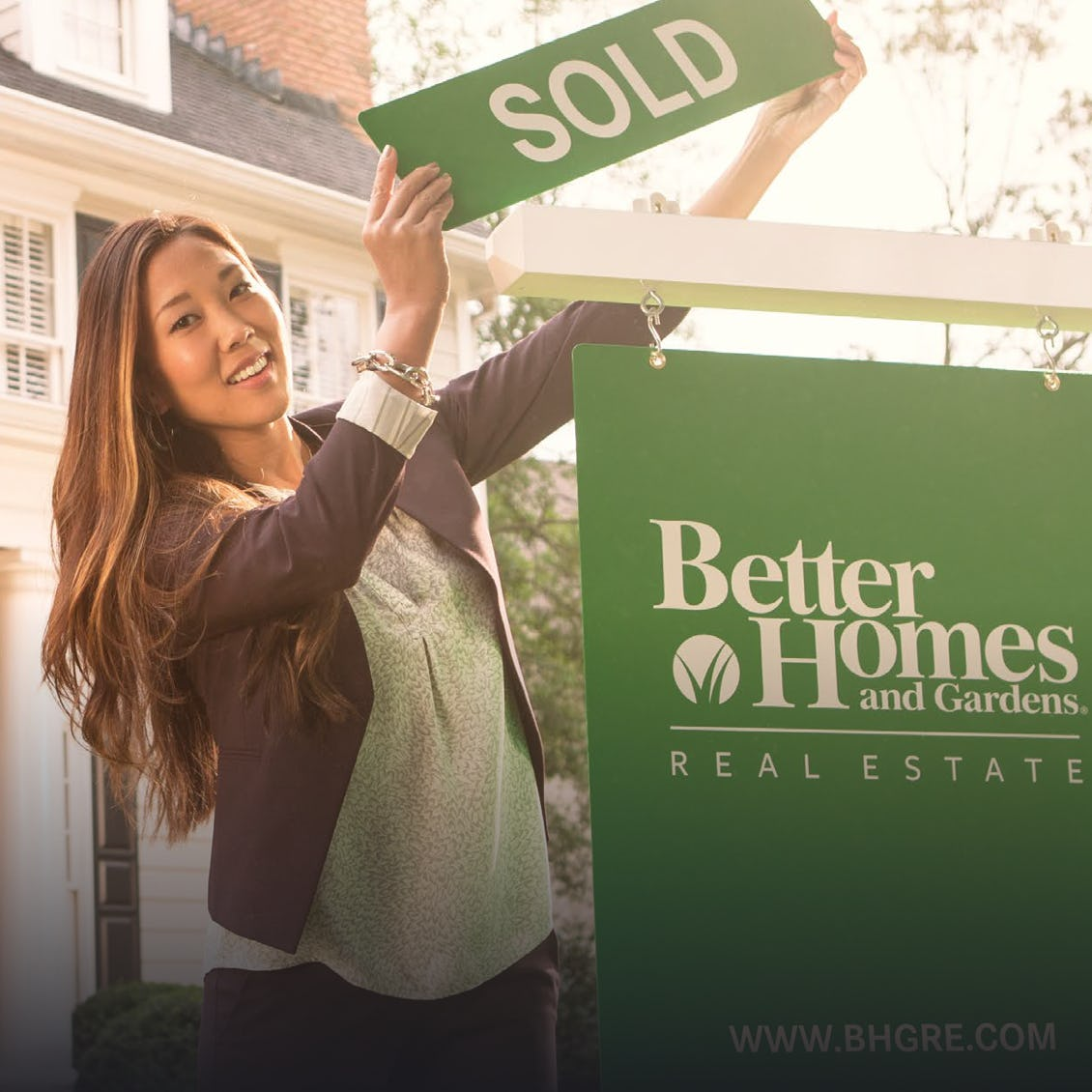 A saleswoman holding a sold sign over a Better Homes and Gardens banner