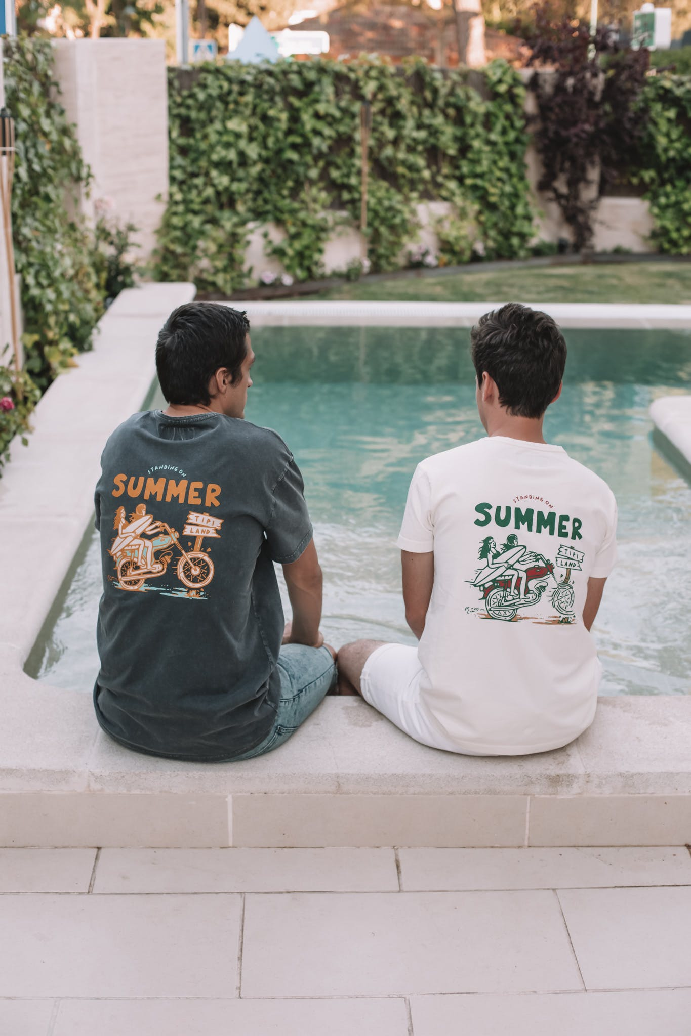 two men sitting at a pool
