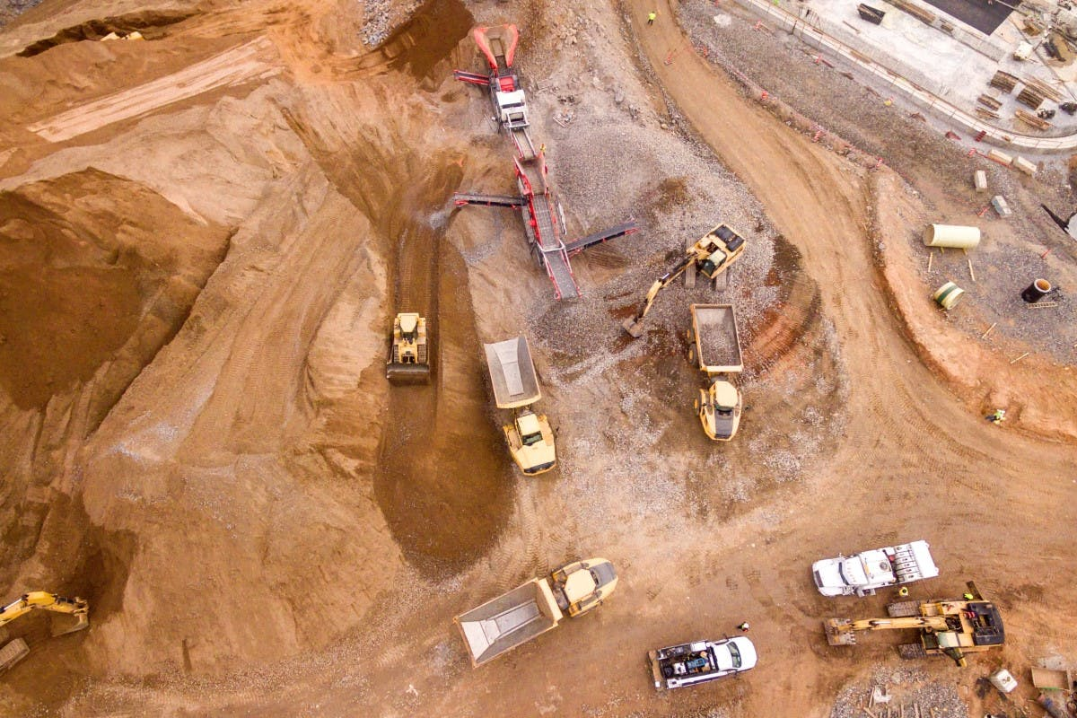 Mining site shown from above, showing machinery and vehicles over brown sandy soil.