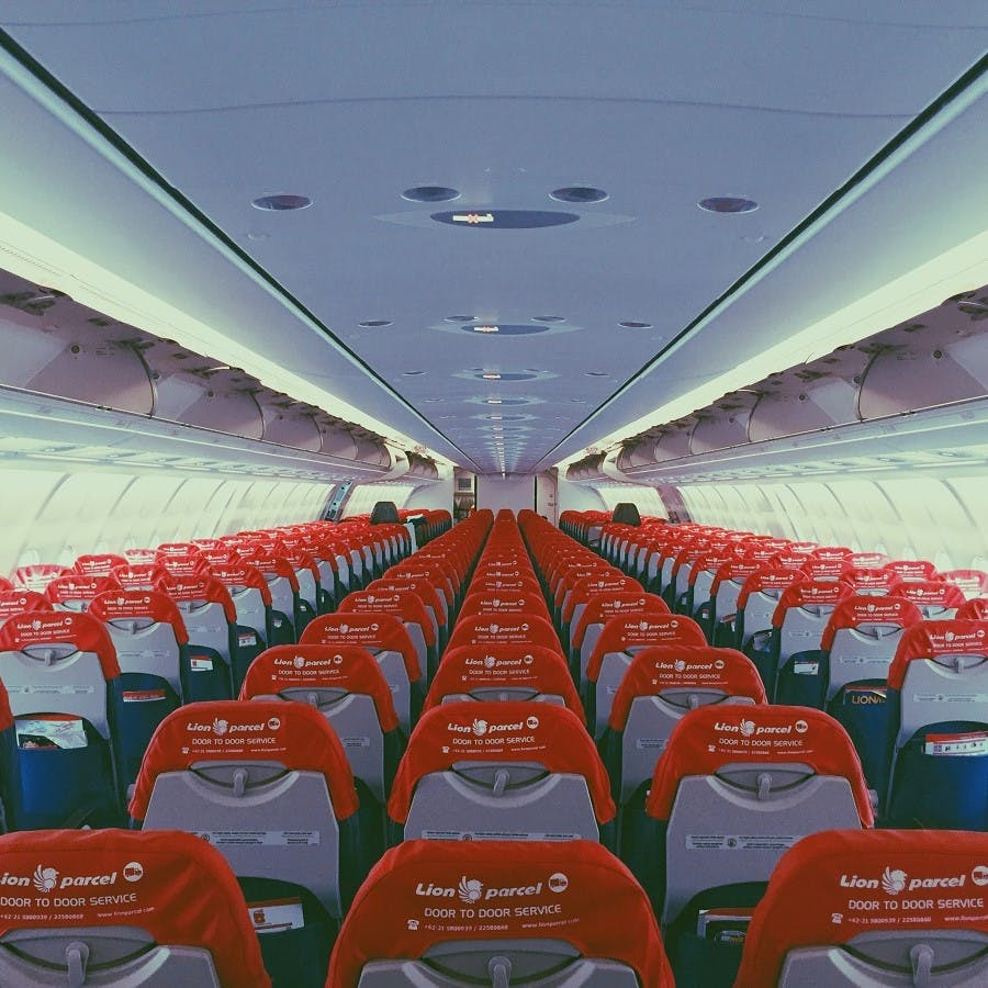 A photo showing the inside of a modern passenger airline plane. The more seats on a flight, the more sustainable the flying.