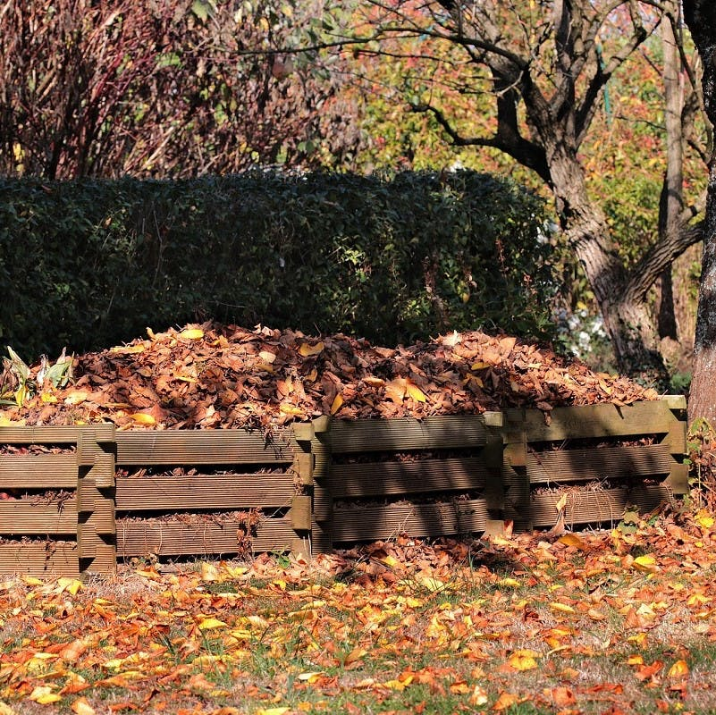 A home composting pile of dry brown leaves