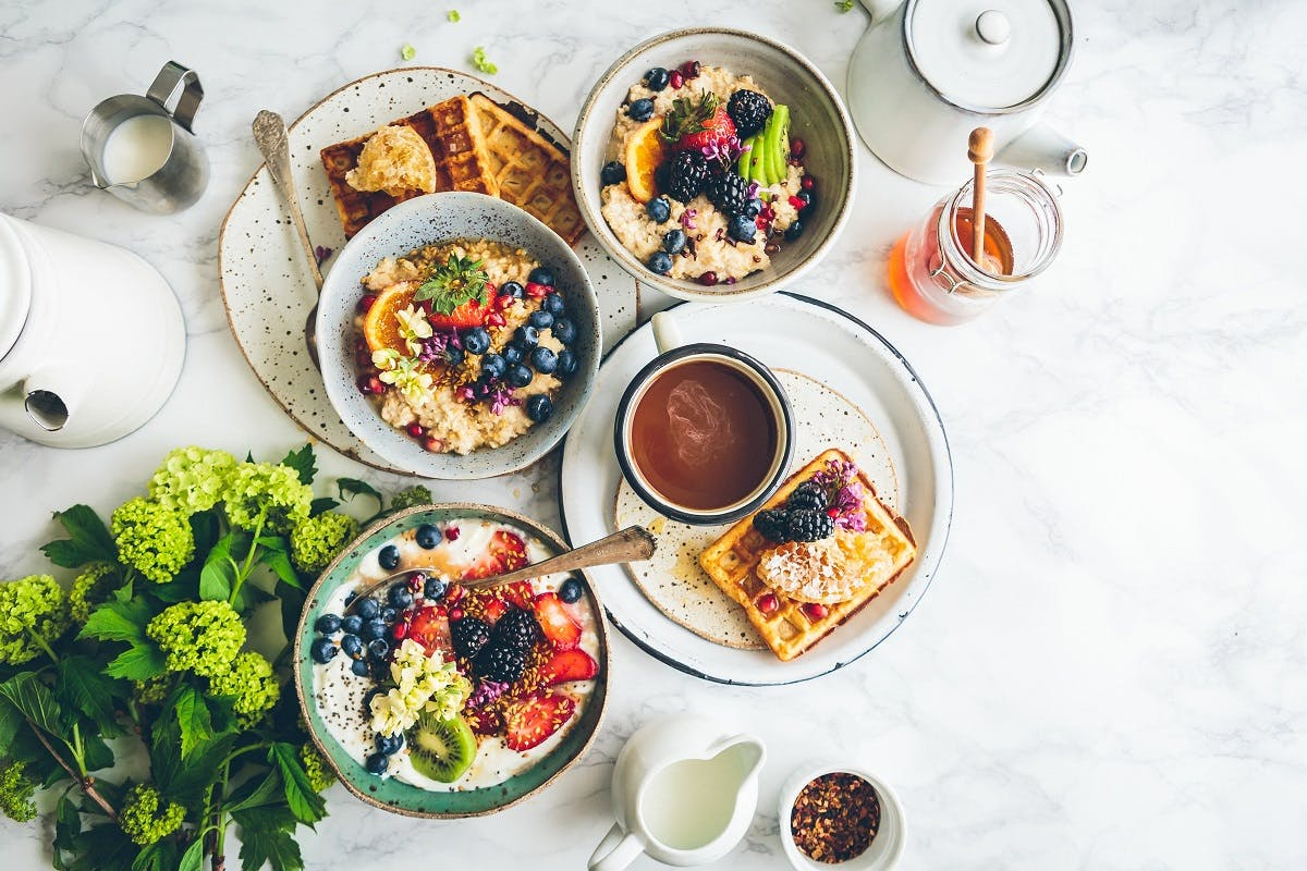 A delicious vegan breakfast comprising of porridge topped with fresh berries, waffles with honey and fresh ground coffee