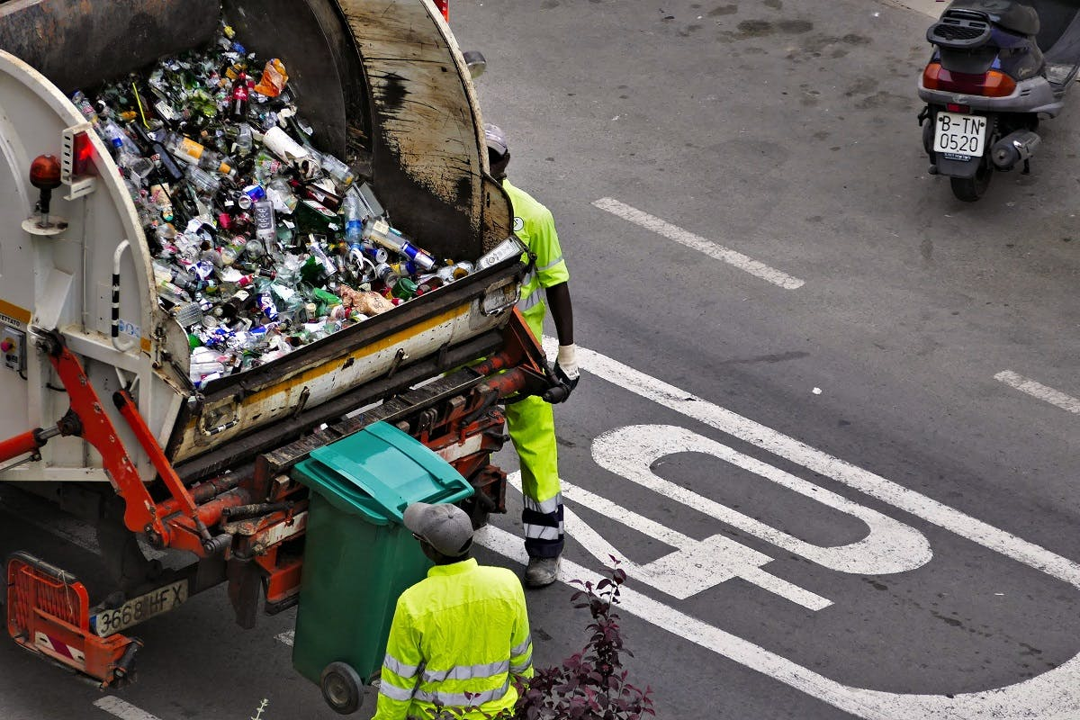 A dustbin lorry collecting recyclable glass bottles.
