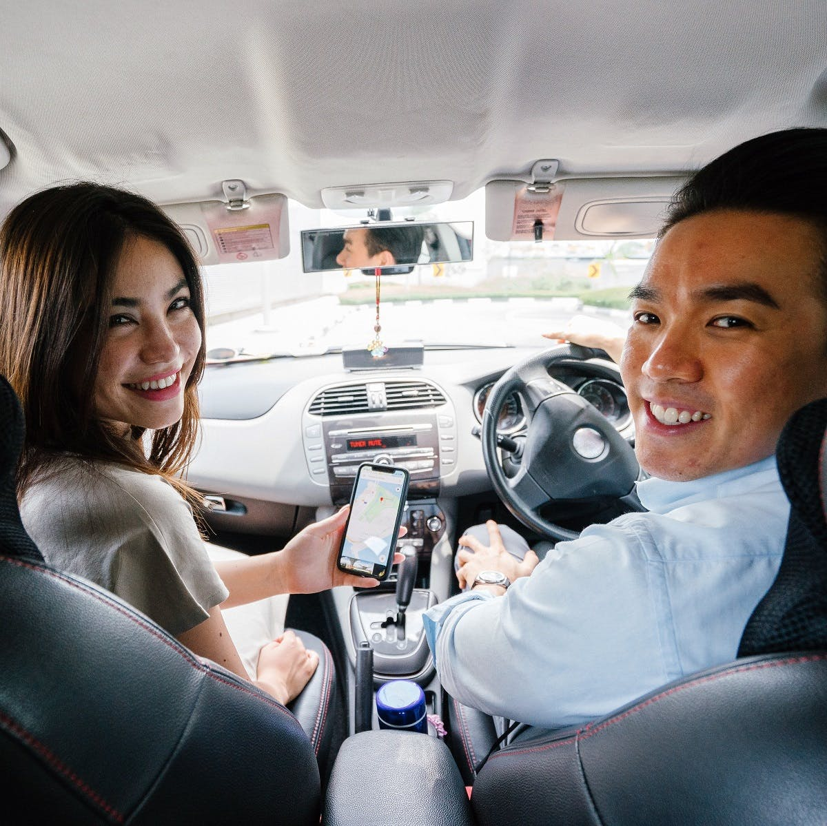 A lady and a man sharing a ride as part of a carpooling scheme. A social and cost saving way to a green commute.