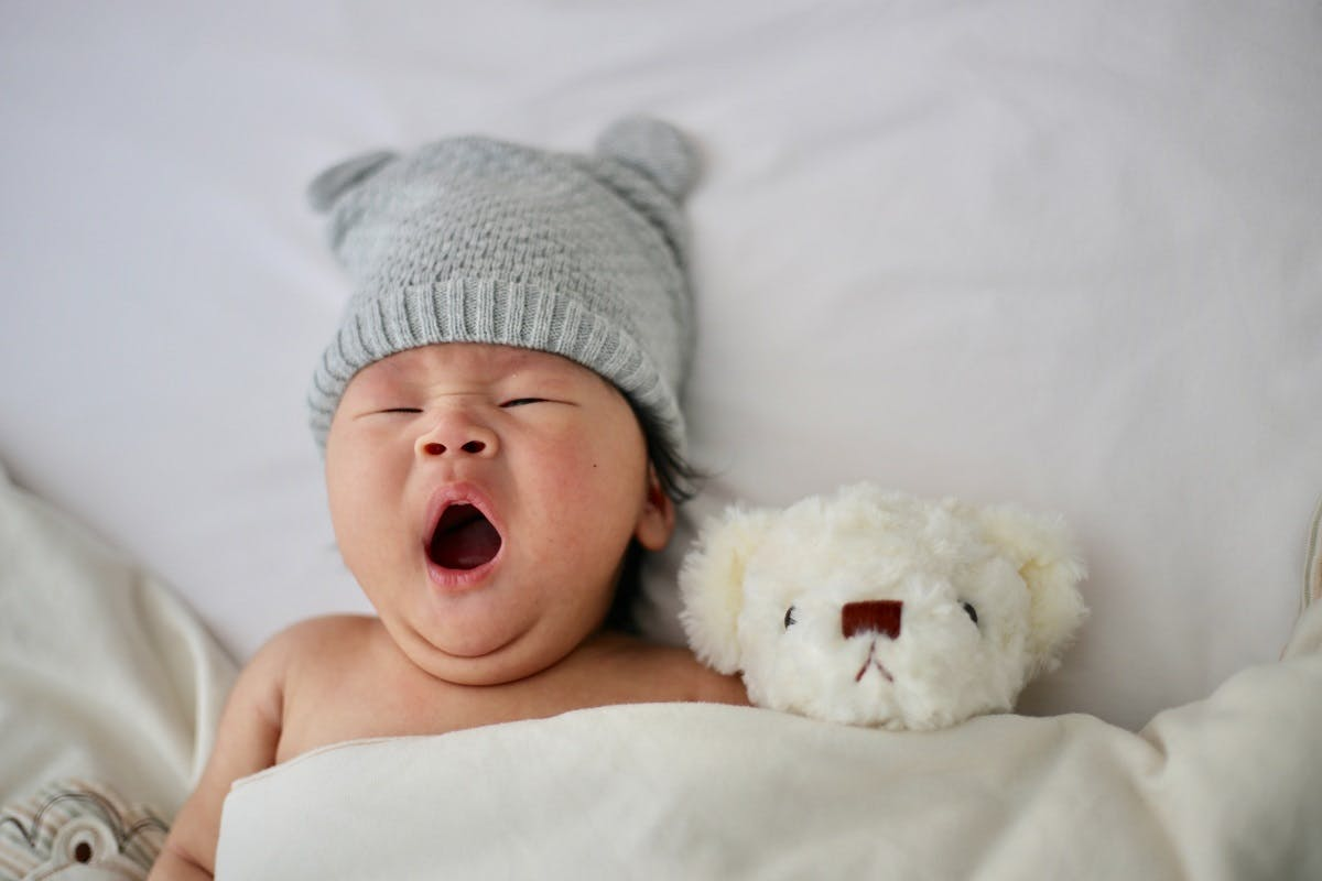 A baby sleeping next to its teddy. Cotton reusables ensure a better night's sleep for your eco baby