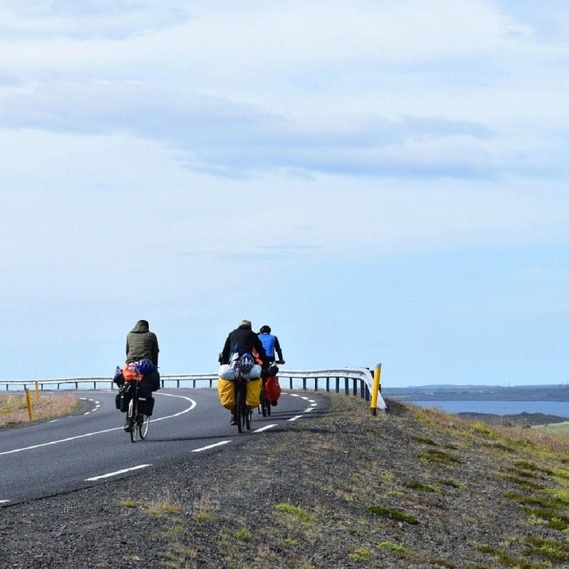Three guys on travelling by bicycle passing beautiful lakes and mountains. Such slow travel is one of the biggest advantages to travelling without flying.