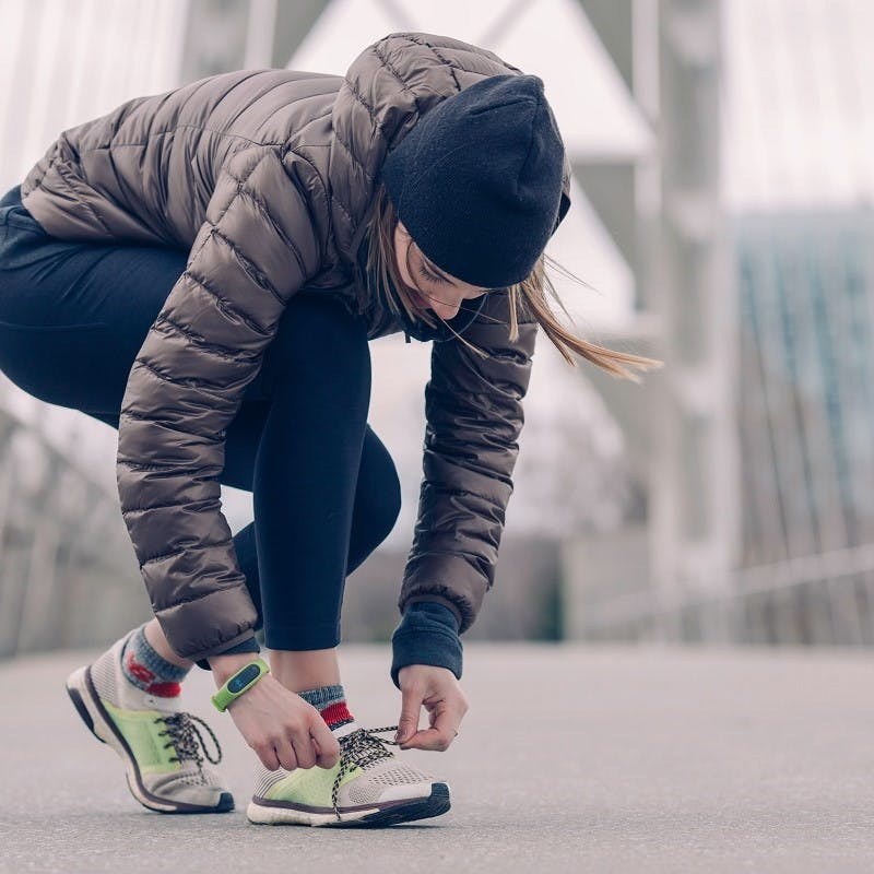 A lady in a beanie, puffer jacket and running leggings, is lacing up her trainers before running or walking to work.