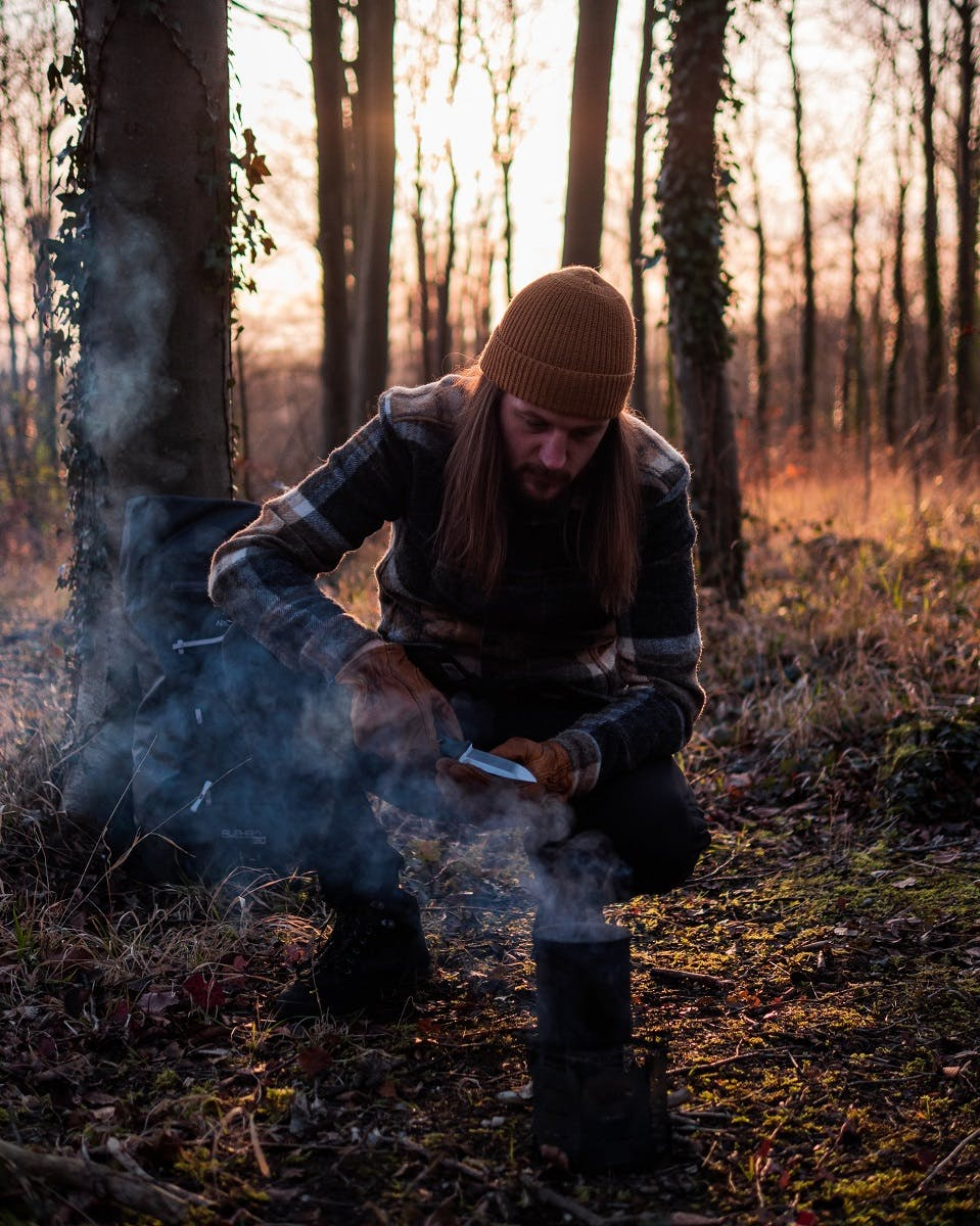 A man enjoying the benefits of slow living by making tea over a camp fire in the woods.