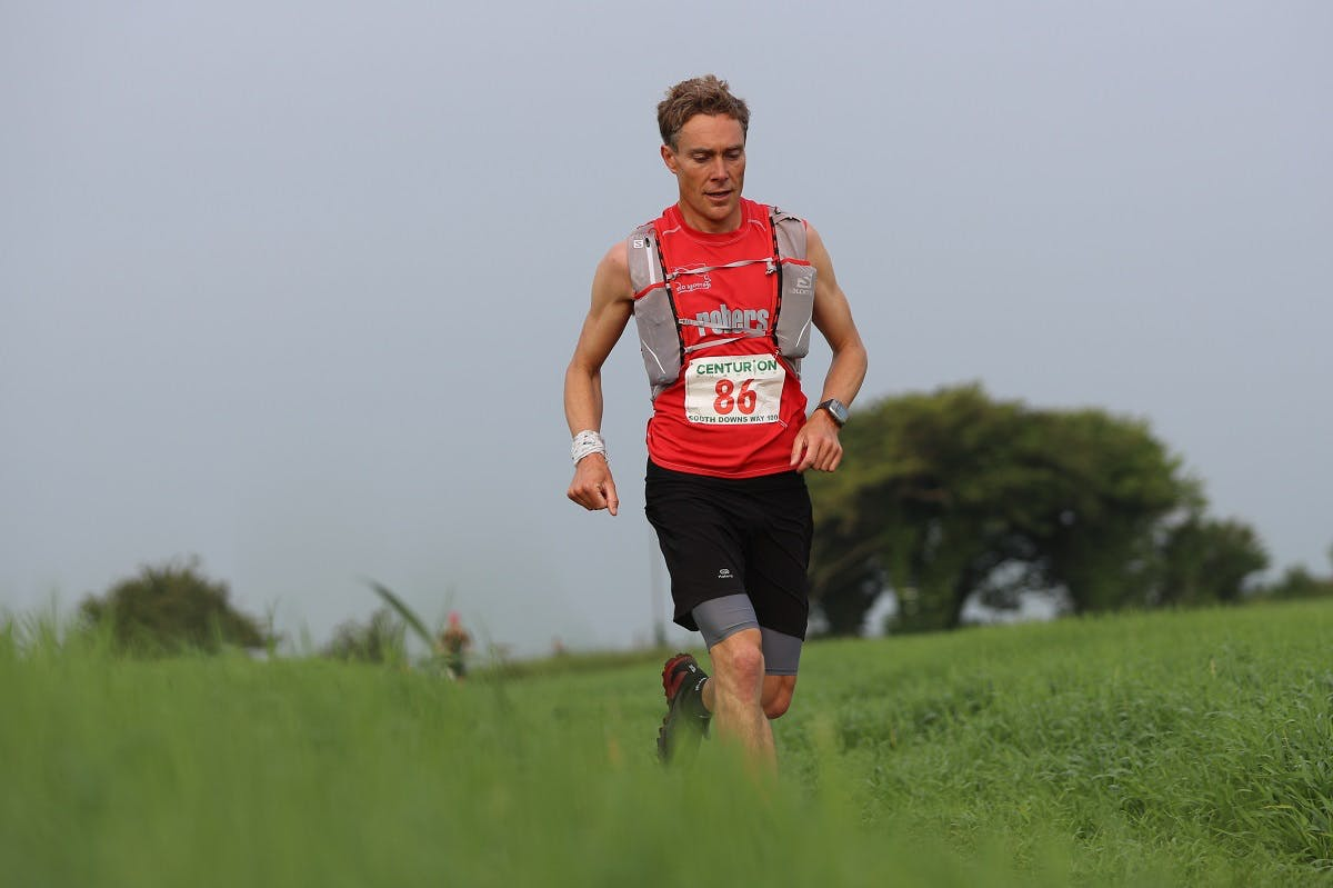 Going vegan doesn't mean you'll lack energy. Here, a plant based ultra trail marathon runner passing over a grassy hill.