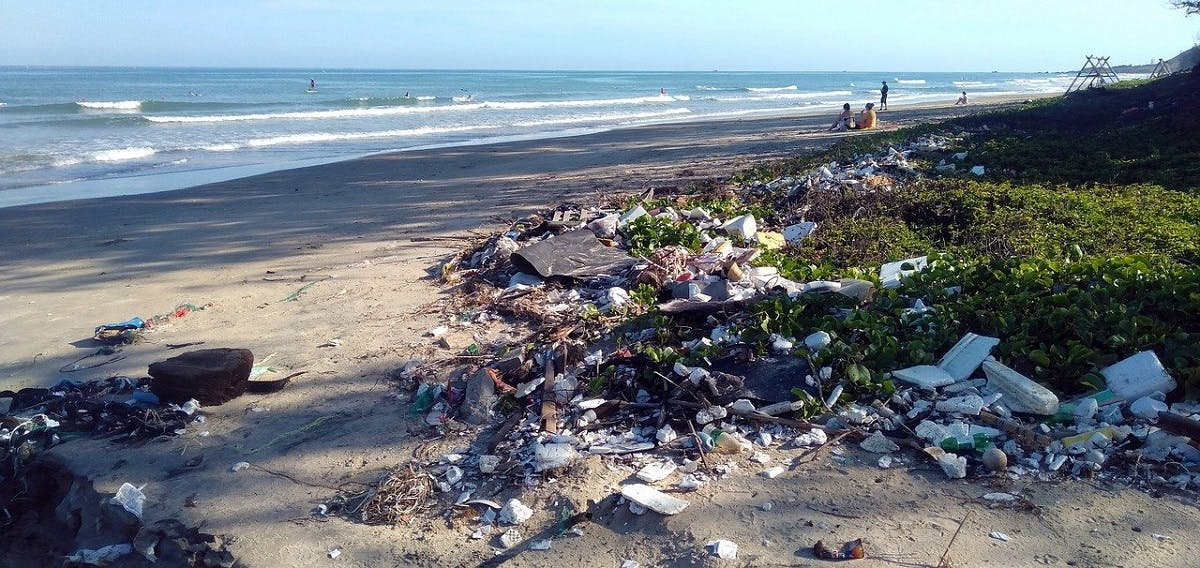 A beach polluted with waste while beach-goers go about their day.