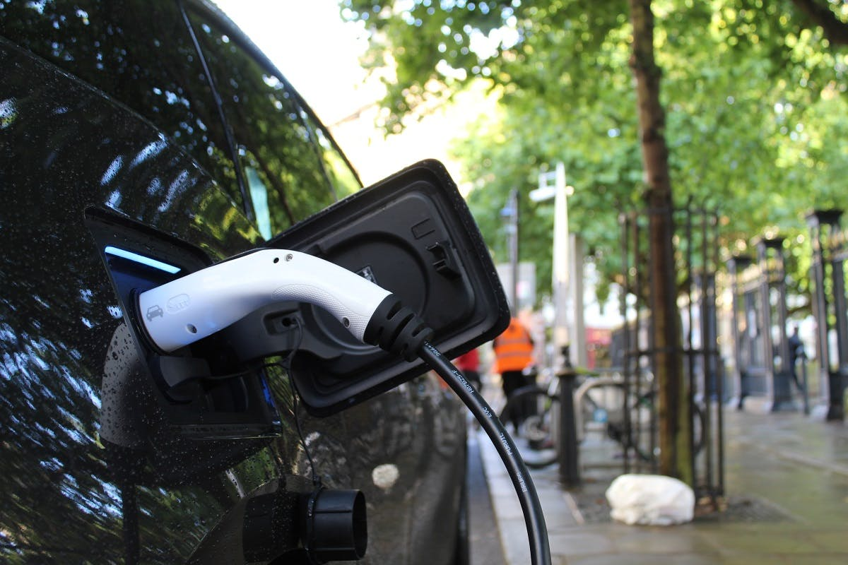 An electric car charging by the side of an urban street.  Convenience of charging vs infrastructure of charging is just one of the many electric cars pros and cons debate.